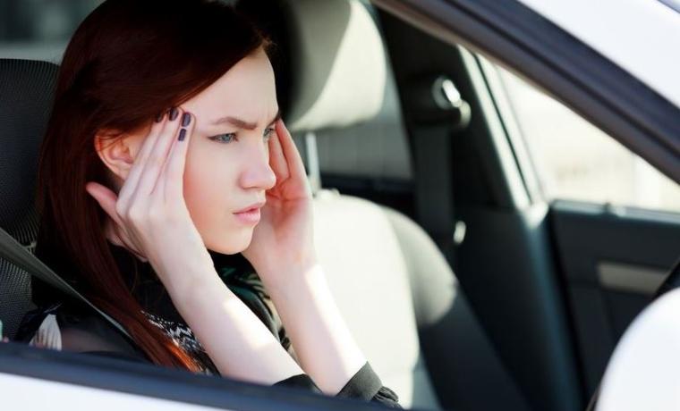 personne au volant avec un mal de tête